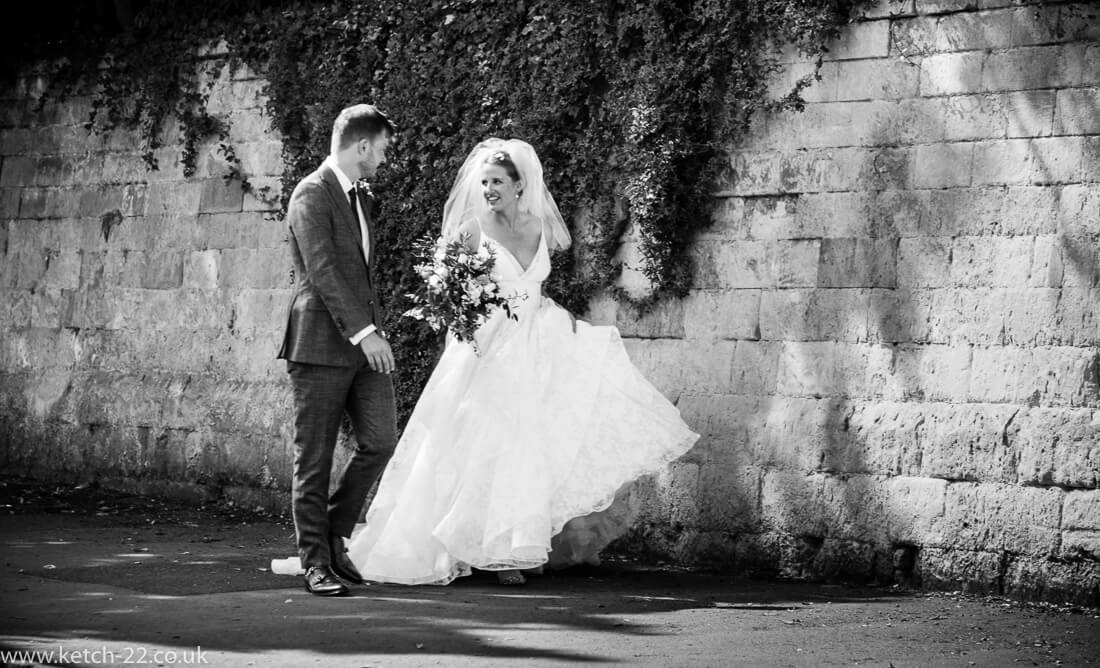Black and white photo of bride and groom walking down street in Winchcombe