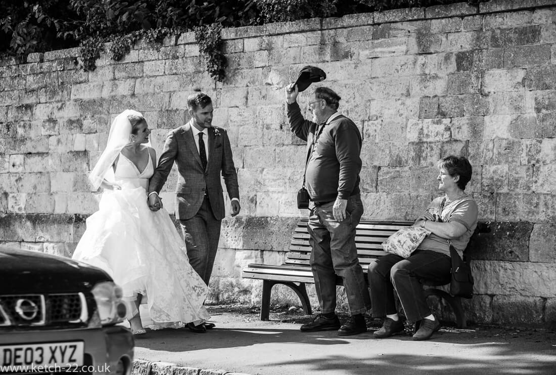 Member of public doffs his cap to bride and groom walking through Winchcombe