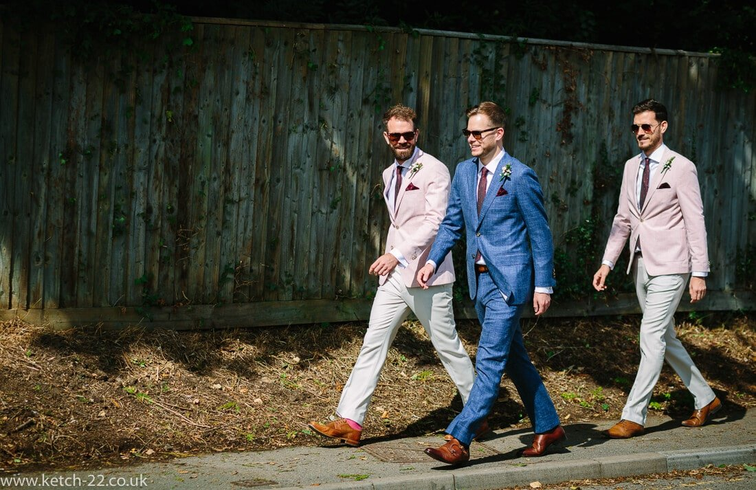 Groom and groomsmen walking along street for Winchcombe Gloucestershire wedding