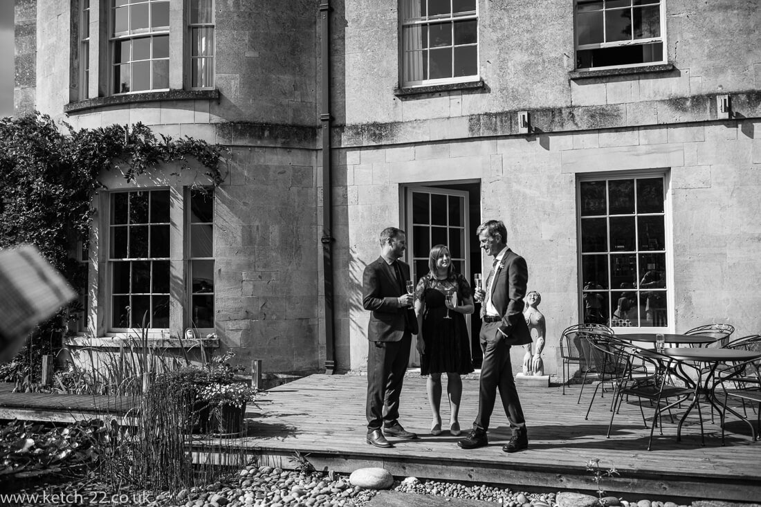 Wedding guests enjoy drinks outside country house
