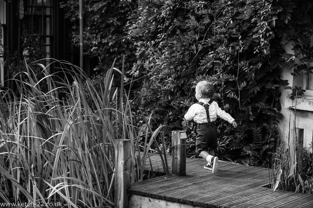 Page boy running in garden at Gloucestershire wedding