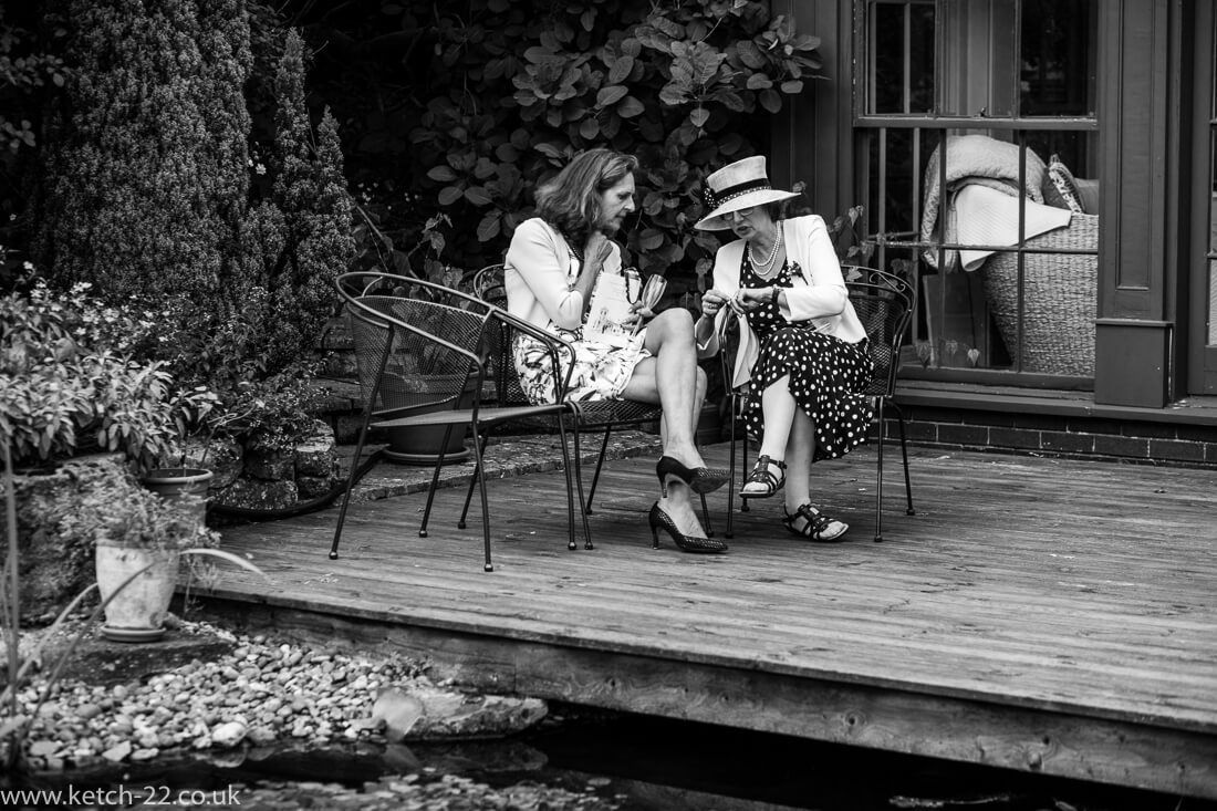 Natural photo of brides mother and friend chatting at wedding reception