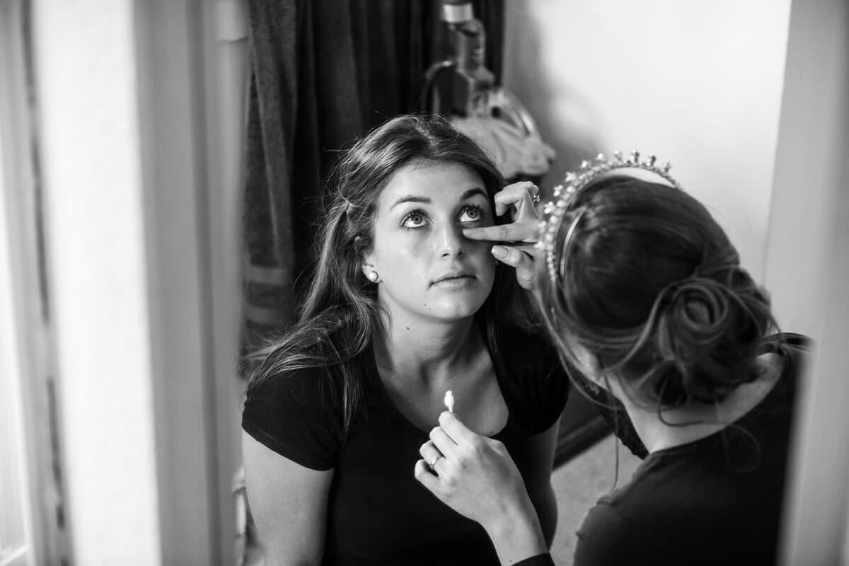 Bride putting makeup on bridesmaid before wedding