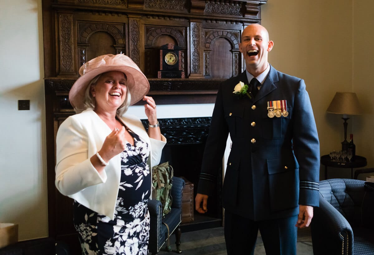 Groom in RAF uniform laughing with wedding guest