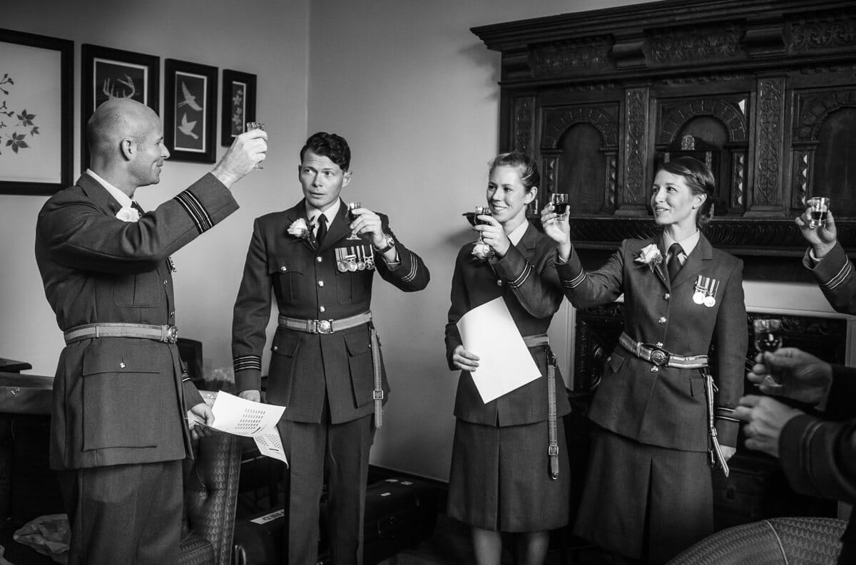 Groom in RAF uniform and friends tosting just prior to wedding