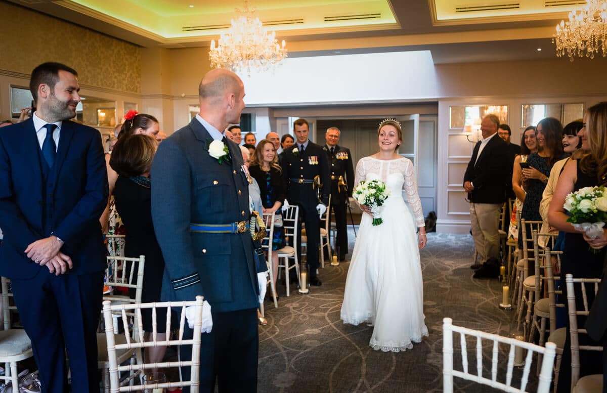 Bride takes her first look at groom in RAF uniform at De Vere Latimer Estate Wedding