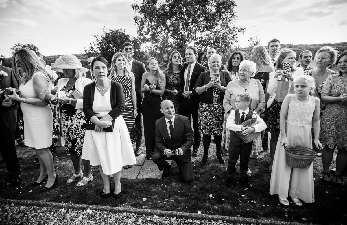 Wedding guests looking up as bride walks down steps