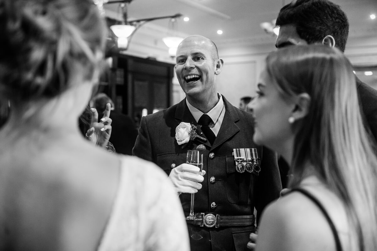 Groom in RAF uniform laughing and chatting with wedding guests
