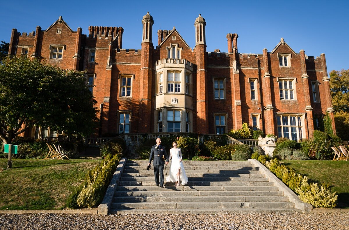 Bride and groom walking down grand steps at De Vere Latimer Estate wedding