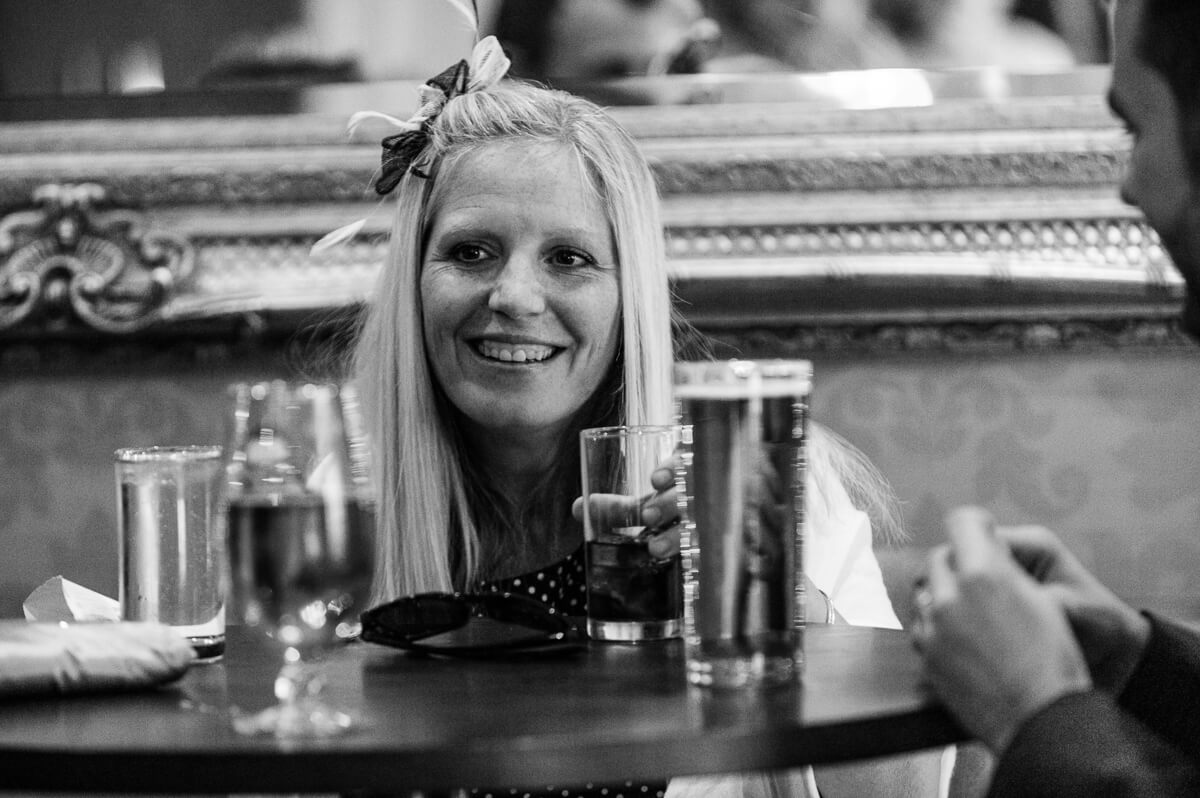 Black and white photo of wedding guest enjoying a drink