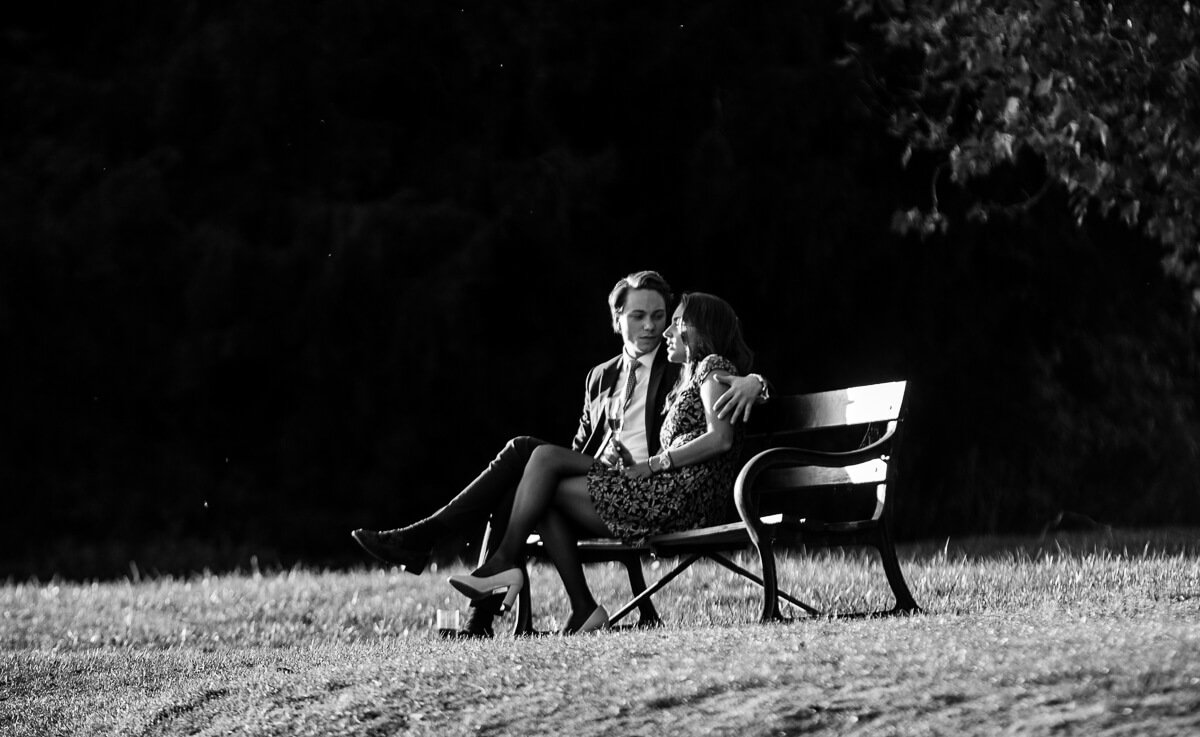 Romantic wedding guests sitting on bench