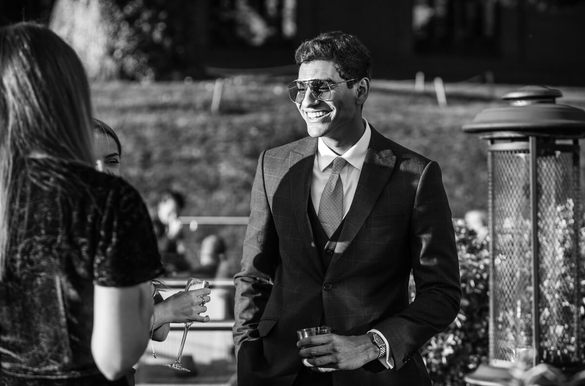 Documentary wedding photo of guest chatting