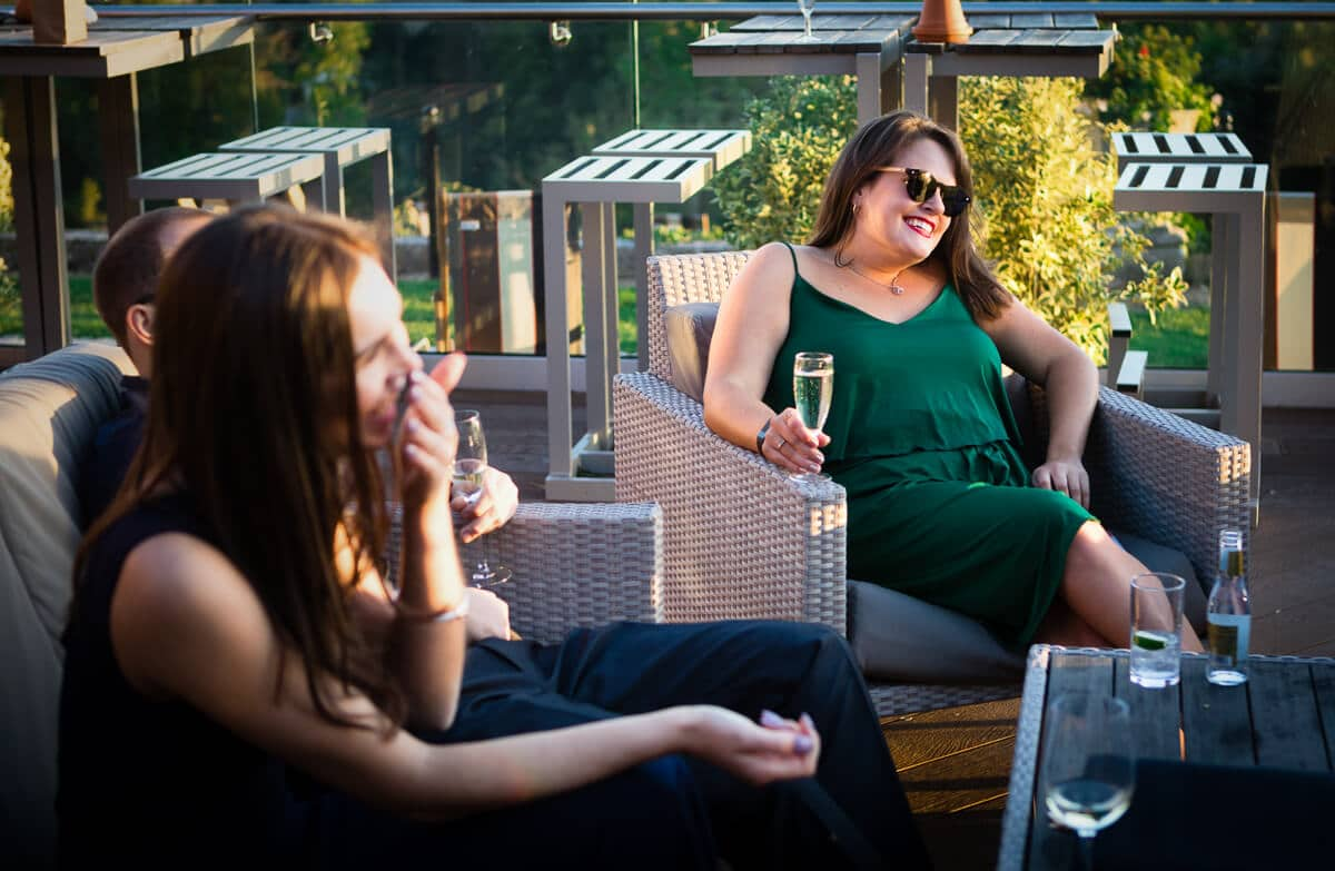 Wedding guest in green dress relaxing and drinking champagne