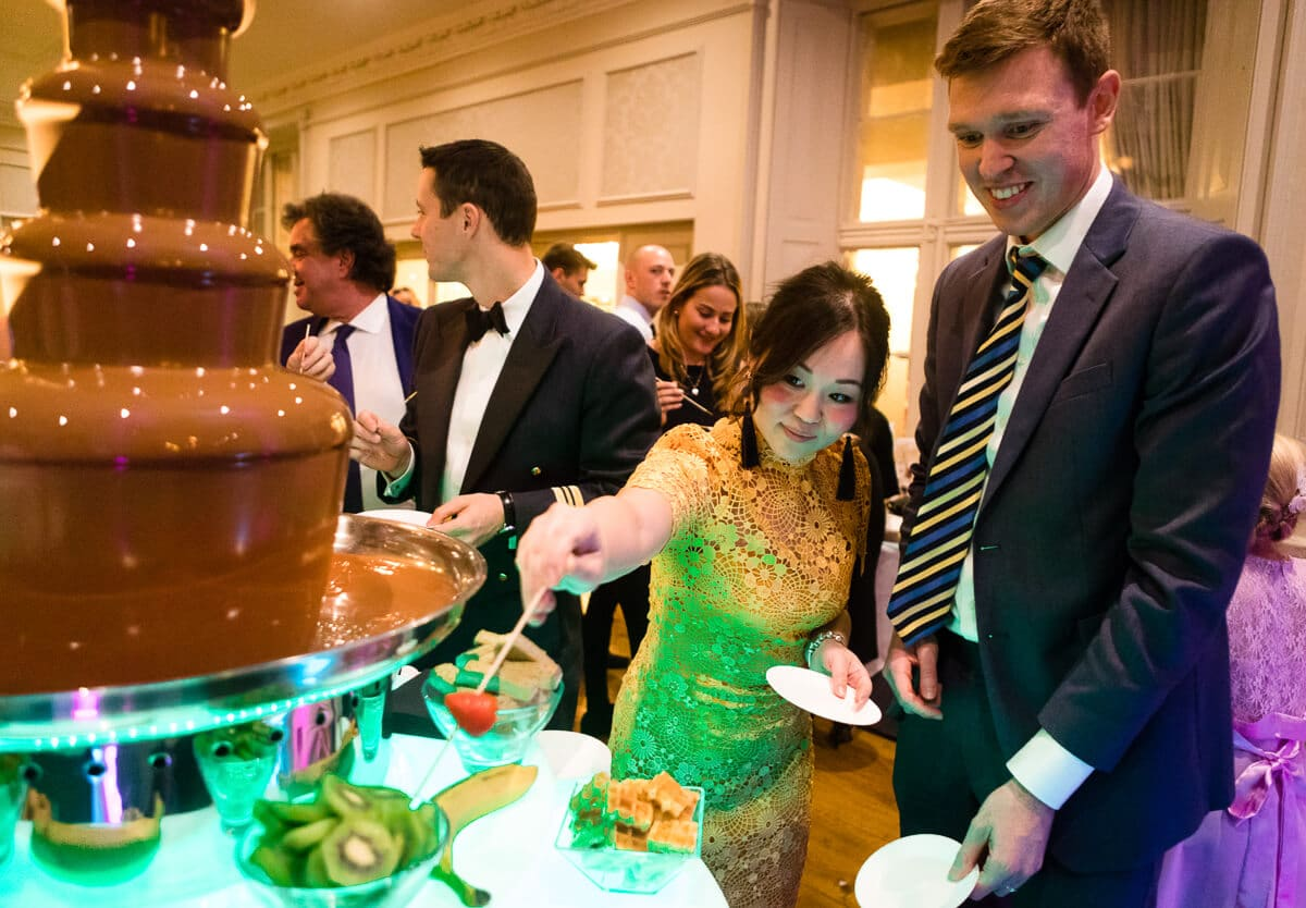 Wedding guests dipping strawberry in chocolate fountain