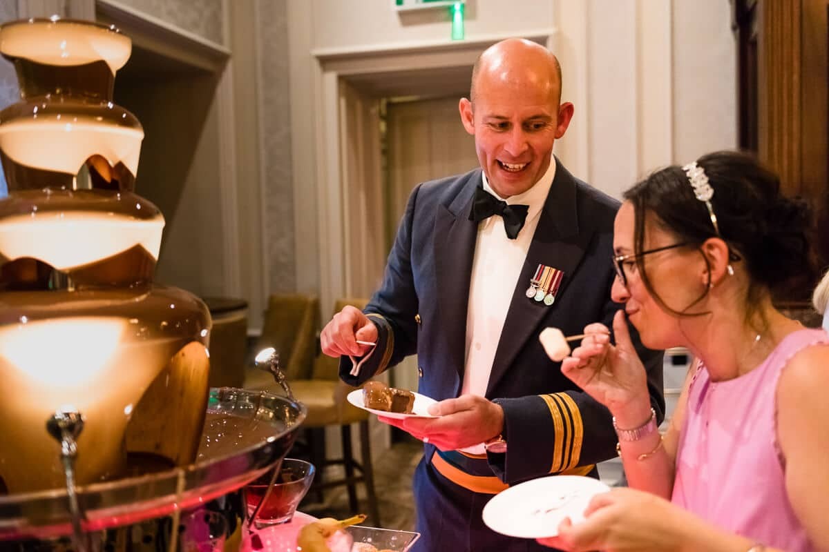 Groom chatting to wedding guest at chocolate fountain