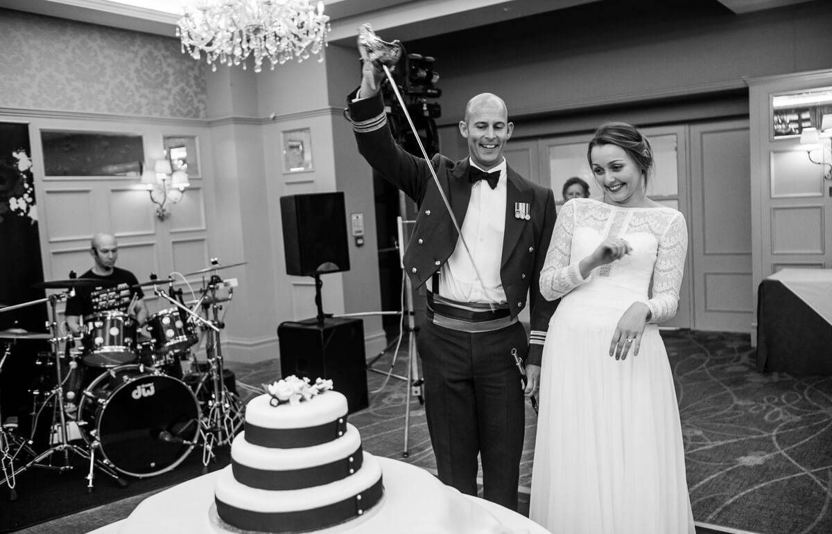 RAF groom and bride playing with sword before cutting the Wedding cake