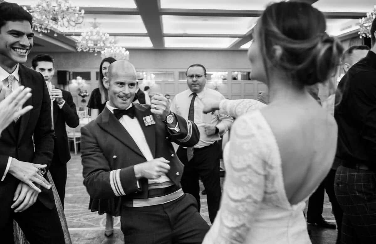 Groom in RAF uniform dancing with his bride at De Vere Latimer Estate wedding