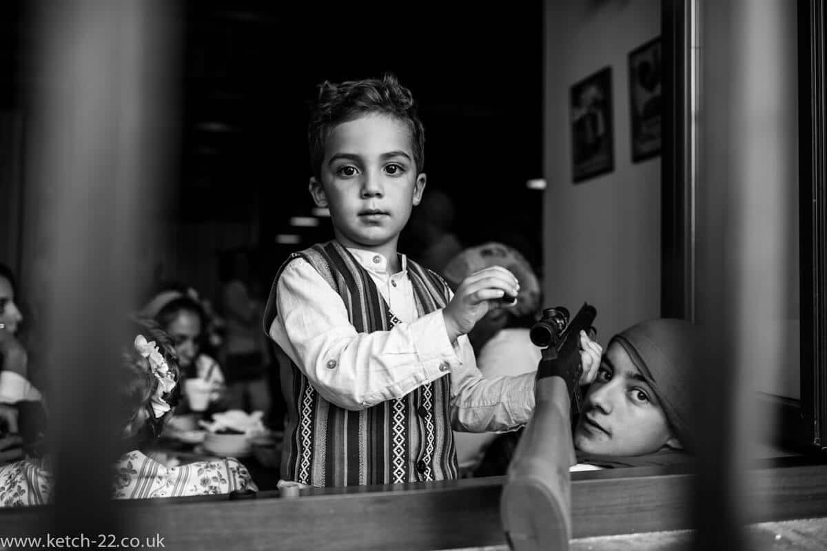 Boy playing with toy gun at fiesta in Grazalema