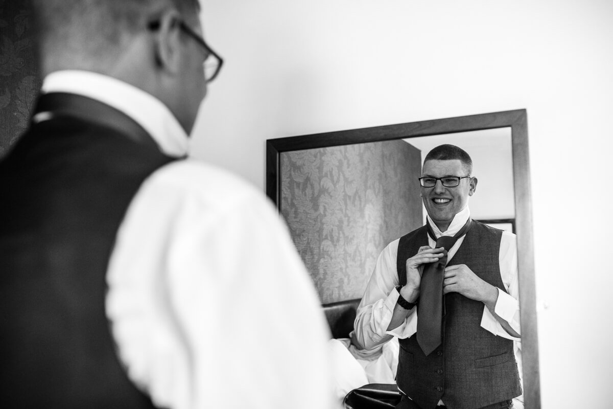 Groom putting on tie in mirror at Gloucestershire wedding