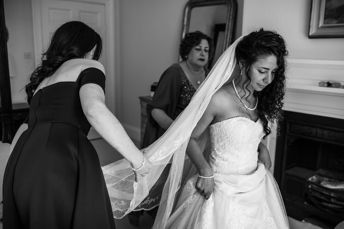 Bride putting on wedding veil