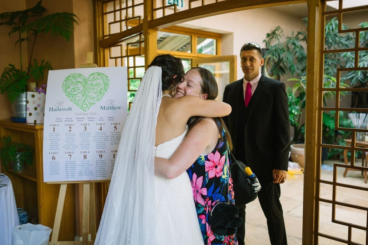 Wedding guest hugging bride after ceremony