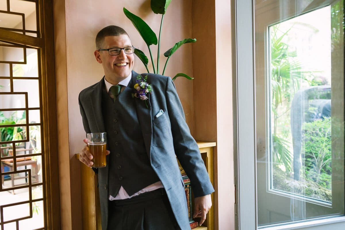 Groom relaxes with a pint after wedding ceremony