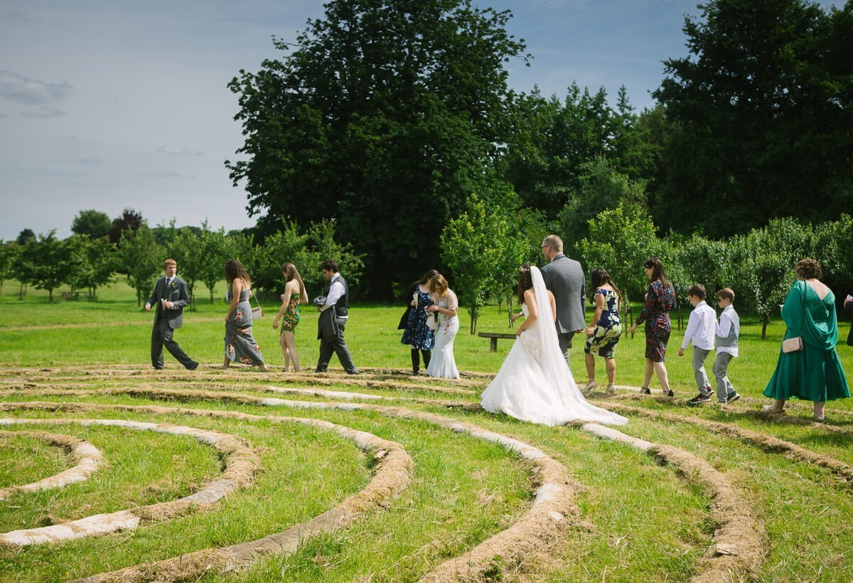 Wedding guest and couple walking around spiral circle