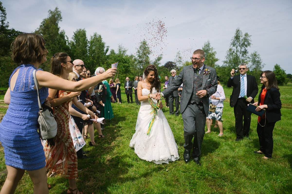 Wedding guests throwing confetti on newly weds