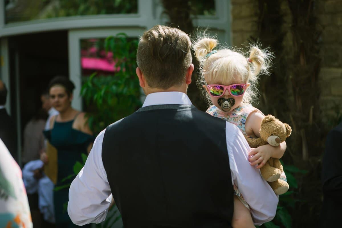 Little girl with blonde hair, pig tails and pink sunglasses at summer wedding