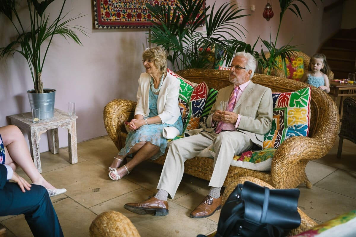 Relatives relax in Palm room at Gloucestershire wedding
