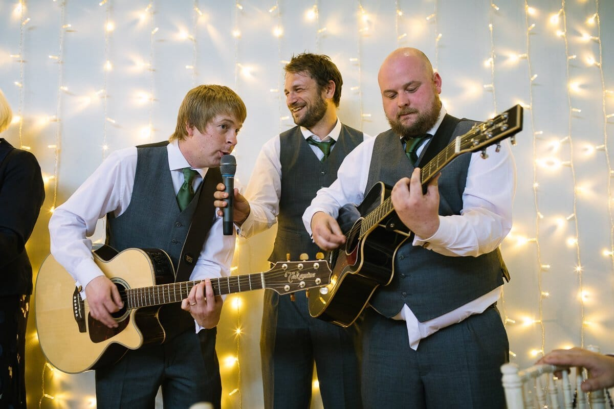 Groomsmen playing guitars at wedding speeches