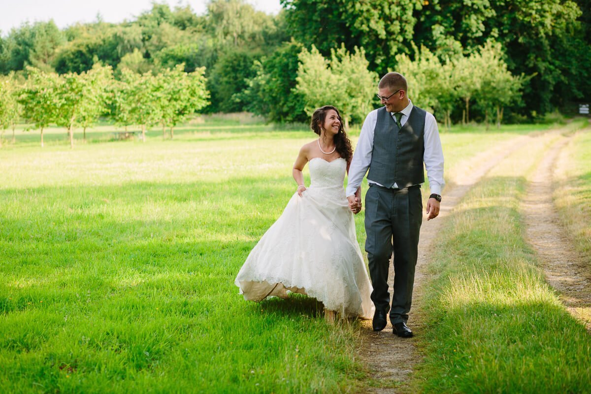 Bride and groom walking in gardens at summer wedding