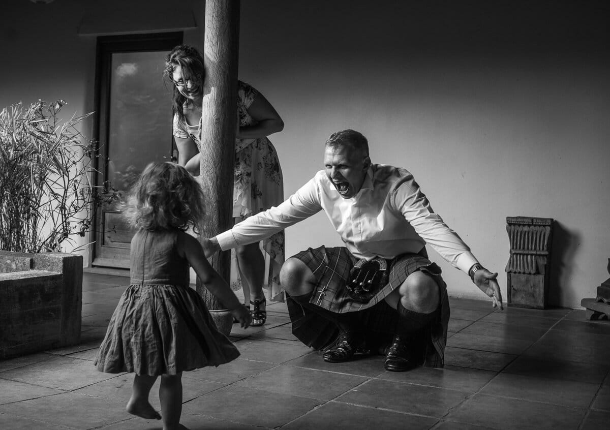 Man wearing kilt playing with his daughter at wedding