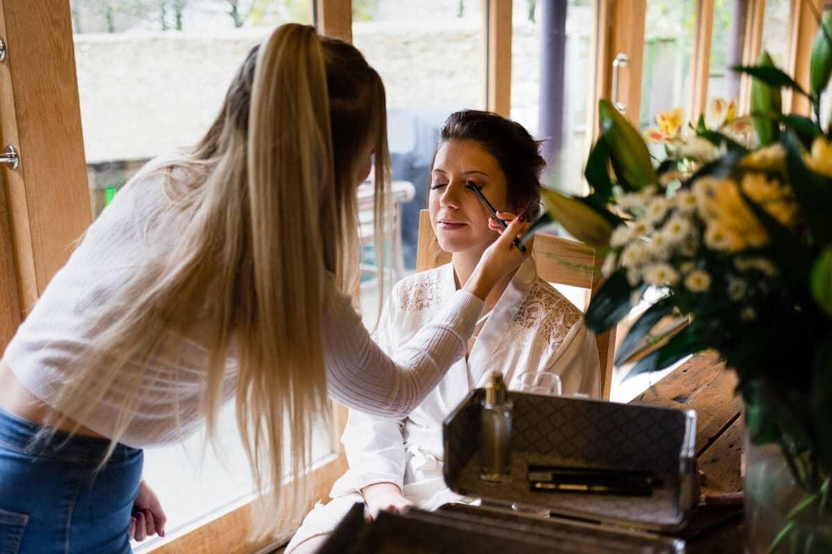 Bride having make up applied at Cripps Barn Wedding