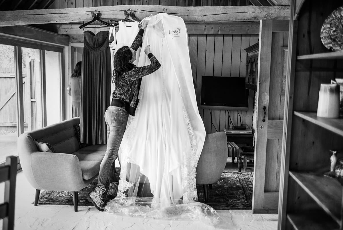 Brides friend hanging up Wedding dress