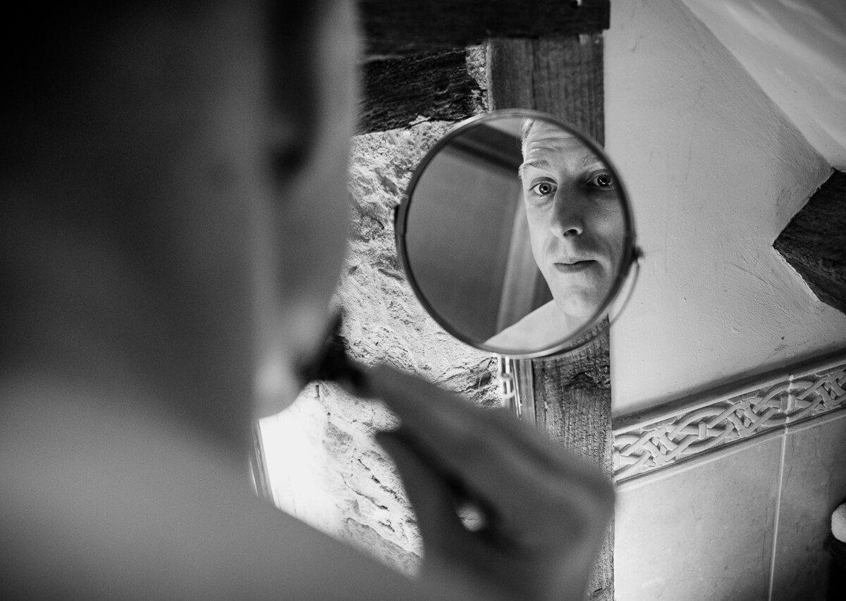 Groom looking in shaving mirror