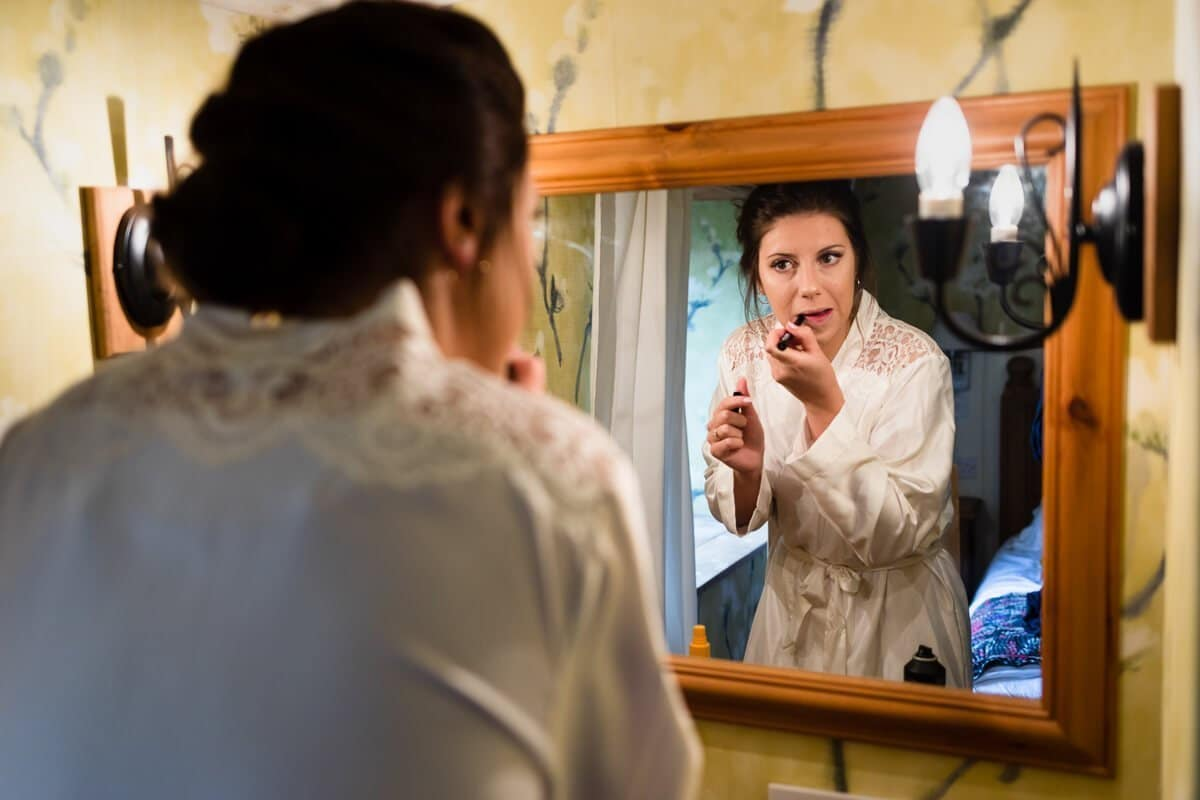 Bride wearing white dressing gown looking in mirror and putting on lipstick