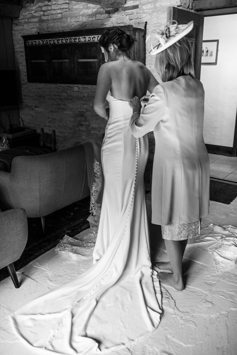 Mother buttoning up back of Wedding dress