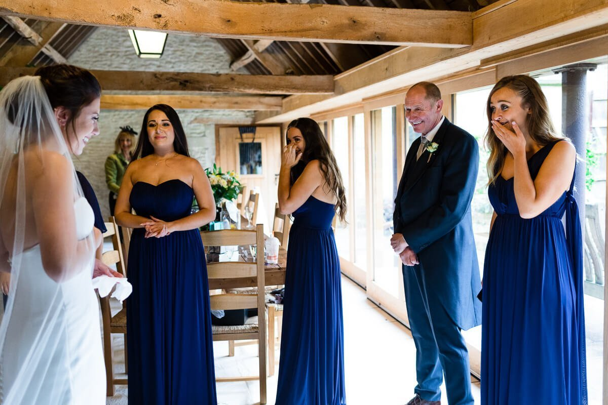 Bridemaids overcome with emotion as they see bride in wedding dress for the first time