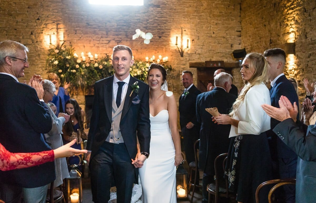 Bride and groom leave ceremony at Cotswold wedding Cripps Barn