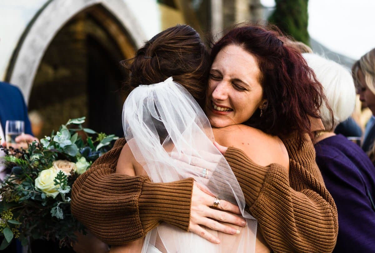 Emotional hug for bride by wedding guest
