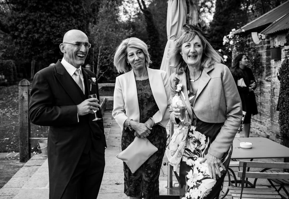 Family rtealxing with drinks and canapes after wedding