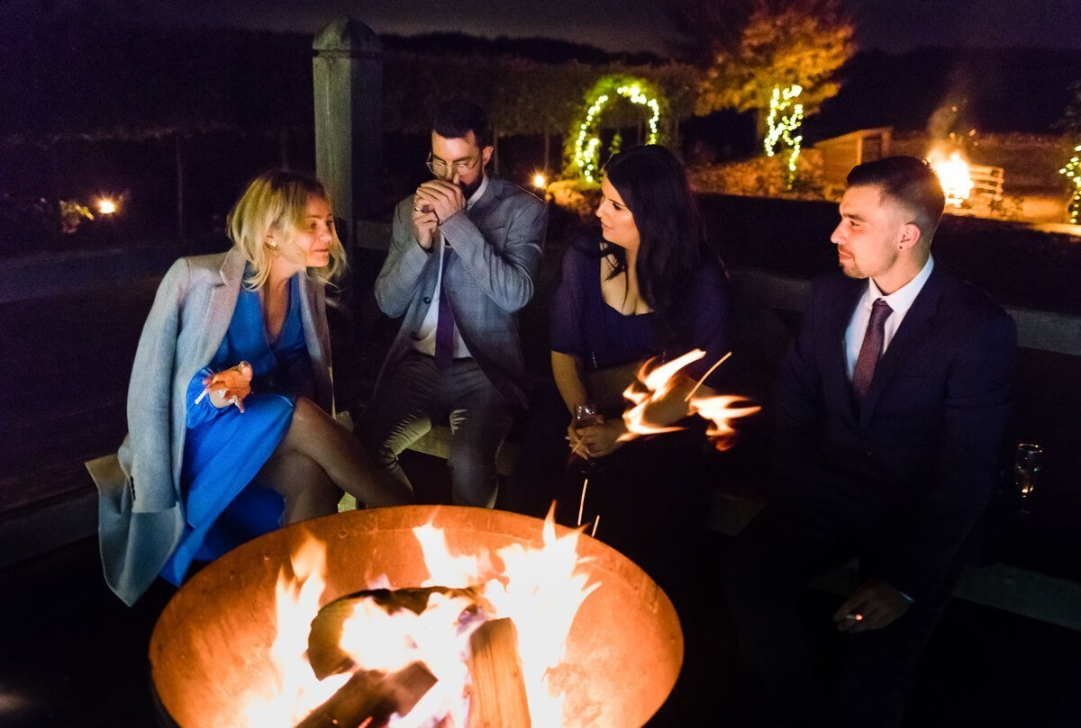 Guests enjoy outside fire at Cotswold Wedding, Cripps Barn