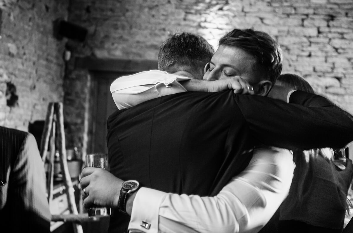 Best man hugging groom at wedding reception
