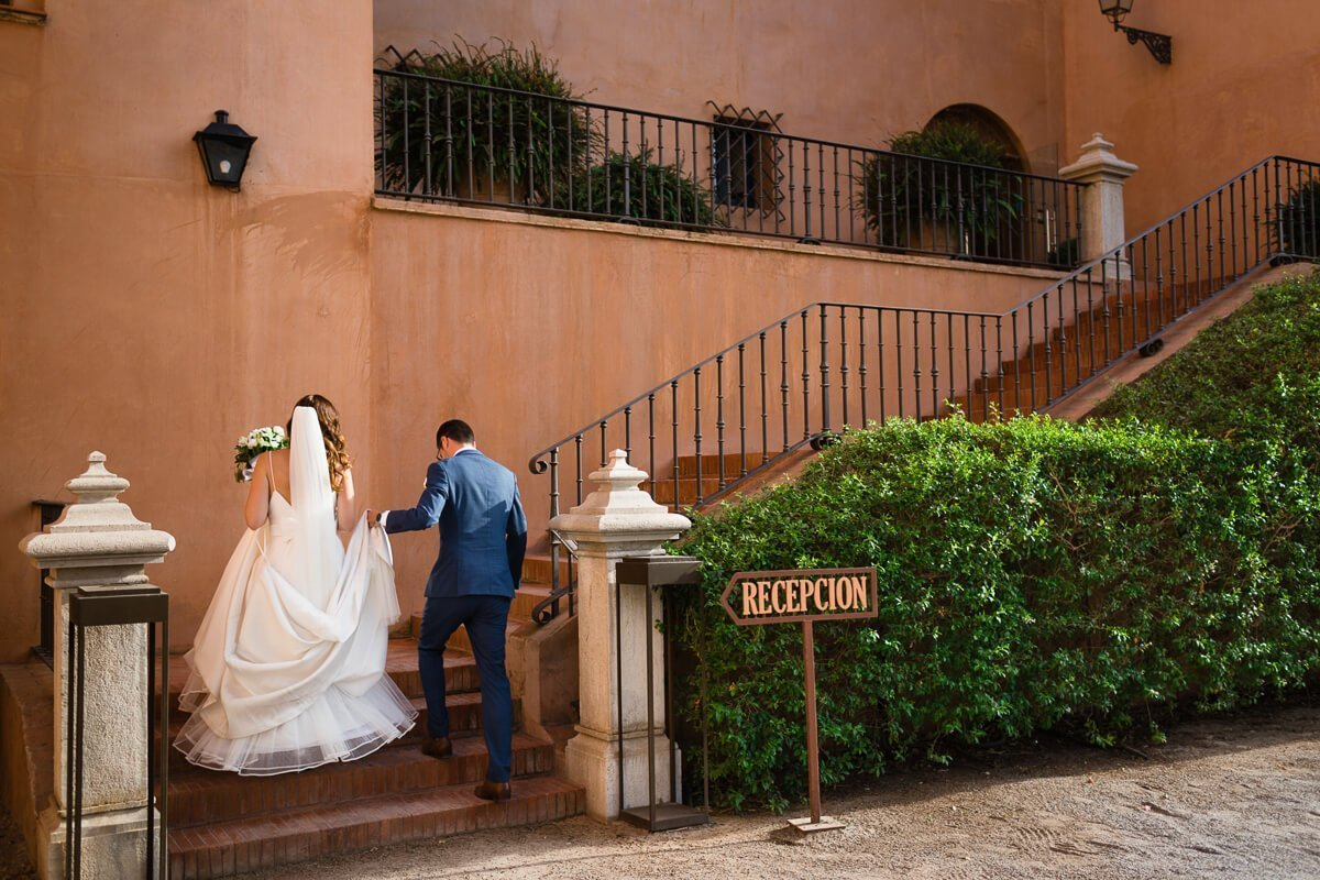 Bride and groom walking up steps at Castillo de Santa Cantalina