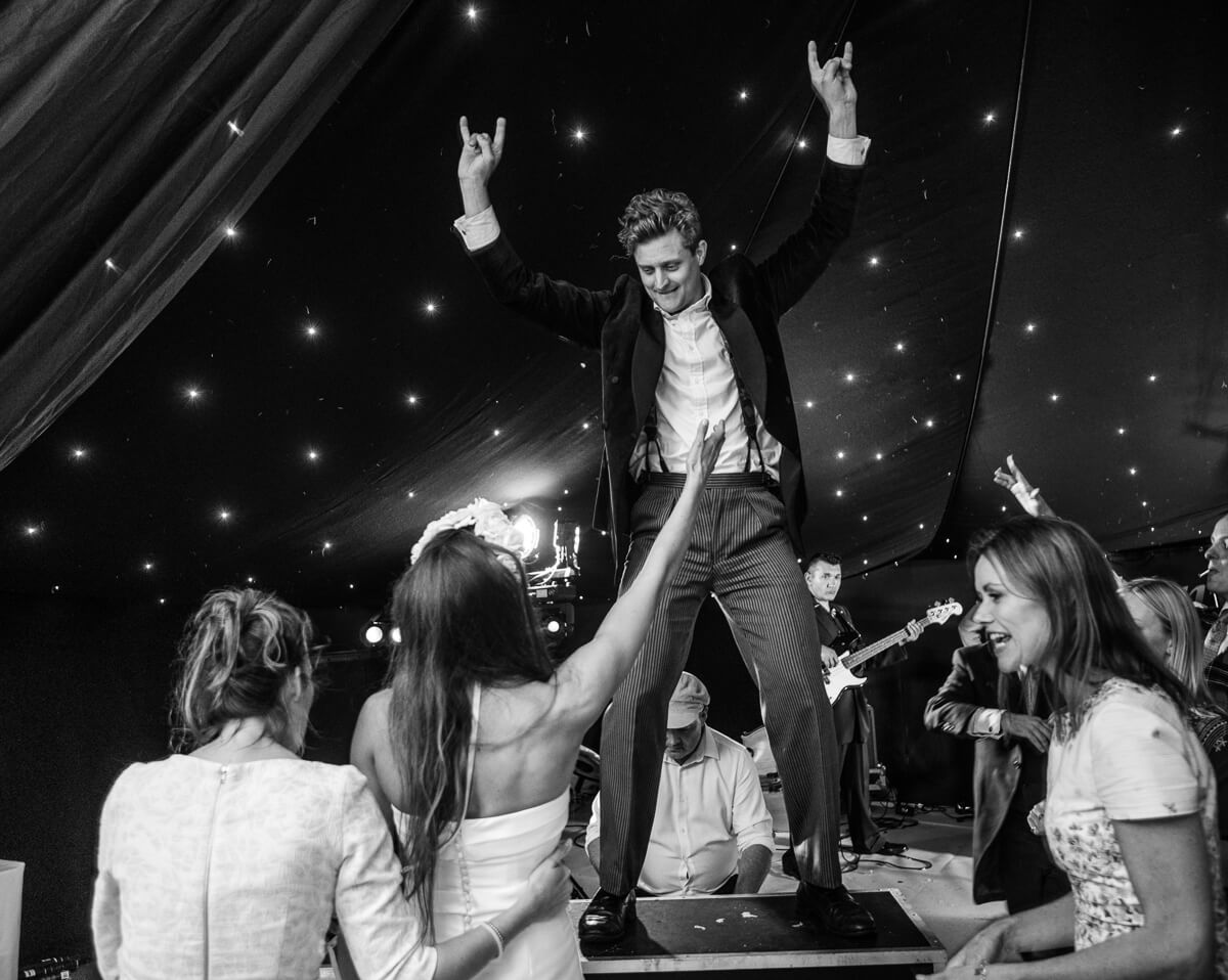 Groom dancing on table at reception